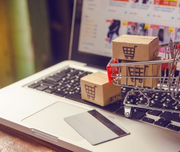 Shopping online concept - Parcel or Paper cartons with a shopping cart logo in a trolley on a laptop keyboard. Shopping service on The online web. with payment by credit card and offers home delivery.